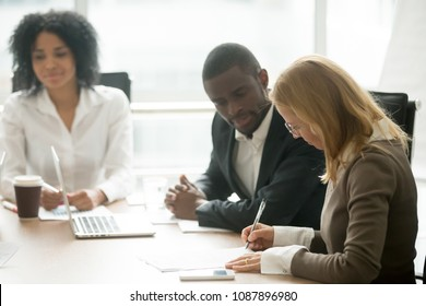 Caucasian businesswoman signing business document making deal at meeting with african partners, female client customer puts written signature on contract buying insurance services, taking bank loan