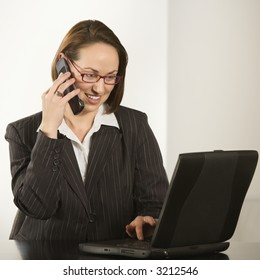 Caucasian businesswoman sitting at desk smiling with laptop computer talking on cellphone.