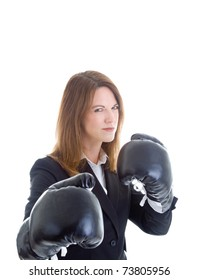Caucasian businesswoman in a suit wearing boxing gloves, ready for a fight.  She's glaring at the camera.  Isolated on white background.