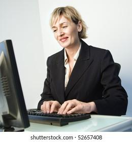 Caucasian businesswoman typing on computer keyboard smiling.