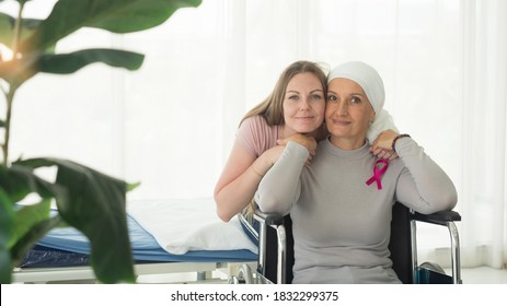 Caucasian cancer patient mother sitting on wheel chair with pretty daughter looking at camera.