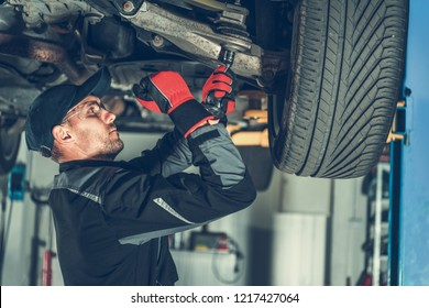 Caucasian Car Mechanic Adjusting Tension in Vehicle Suspension Element. Professional Automotive Service.