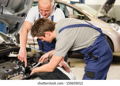 Caucasian car mechanics working together in garage