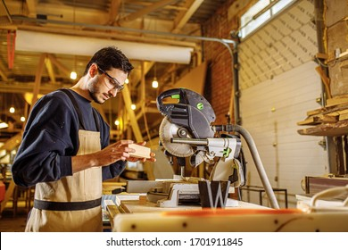 caucasian carpenter preparing wooden furniture for customers, work on an order, use electric machine for sawing and cutting, handicraft, carpentry concept
