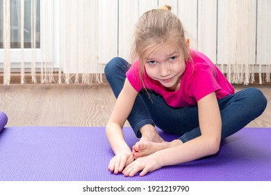 Caucasian charming little girl doing fitness exercises at home. Stretching exercises. Kids fitness concept.