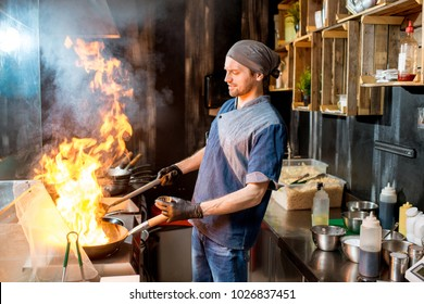 Caucasian chief cook cooking on the wok pan with flambe on the asian restaurant kitchen