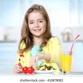 Caucasian child girl eating fresh salad tomatoes drinking orange juice indoors sitting at  kitchen table.Kid healthy food nutrition concept.