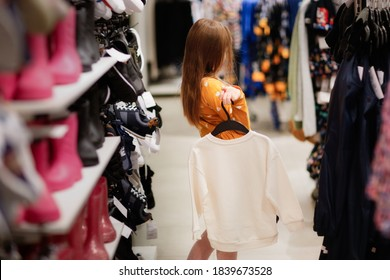 Caucasian child girl with long blonde hair in store examines and chooses clothes and dresses, children's shopping