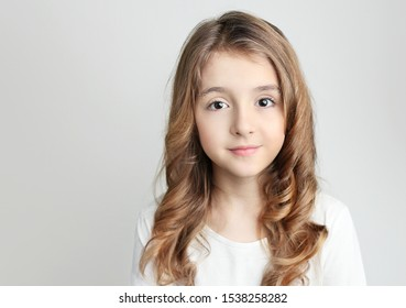 Caucasian child girl portrait on grey background closeup face.Beautiful teenager long hair kid in white clothing.