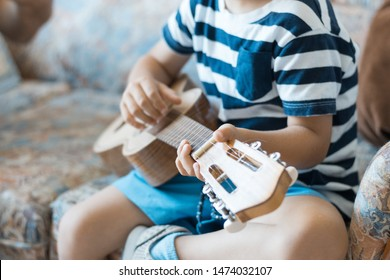 Caucasian child playing and making music chords with small guitar or ukulele, close up