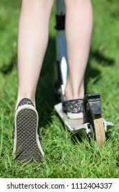 Caucasian child riding puch scooter on green grass, close-up view
