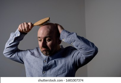 Caucasian confused bald man trying hair brush. Problem with men's hair
