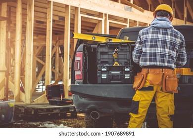 Kaukasischer Bauauftragnehmer in seinen 40ern und sein moderner Black Pickup Truck. Männer bereiten seine Werkzeuge für die Arbeit vor. Holzhausskelett auf Hintergrund.