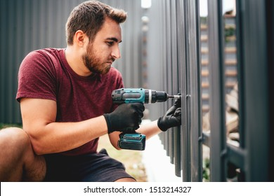Caucasian construction man working with cordless electrical screwdriver on metal fence - Shutterstock ID 1513214327