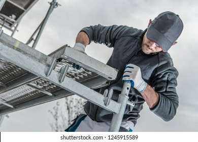 Caucasian Construction Worker Installing Scaffolding Elements.