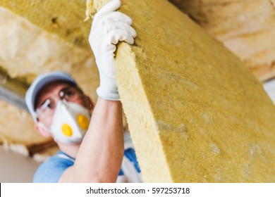 Caucasian Construction Worker with Piece of Insulating Material, Roof Insulating by Mineral Wool.