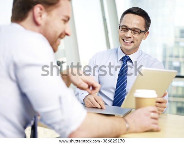 caucasian corporate executive responding to coworker with a big smiling during a conversation in office.