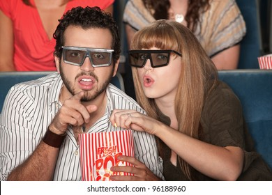 Caucasian couple with 3D glasses and popcorn watch a movie