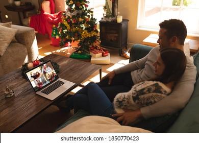 Couple de Caucasiens à noël, assis sur un canapé à la maison, se réjouissant d'avoir une discussion en vidéo avec ses amis et sa famille sur un écran d'ordinateur portable. distanciation sociale pendant la pandémie du vif 19 à noël.