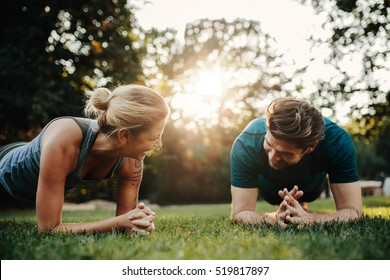 Caucasian couple doing core workout together in park. Fit young man and woman exercising.
