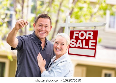 Caucasian Couple in Front of For Sale Real Estate Sign and House with Keys.