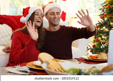 Un couple de Caucasiens à la maison, faisant un appel vidéo à noël, assis à table pour le dîner de noël, portant des chapeaux de santa, souriant et agitant avec un arbre de noël. temps de qualité ensemble dans le covid