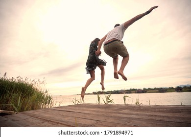 caucasian couple jumping together in the river holding hands