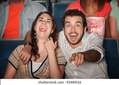 Caucasian couple laugh out loud in theater