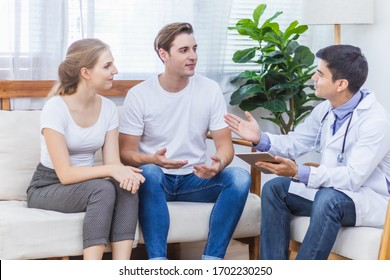 Caucasian couple patient husband and wife visit or meeting male doctor for pregnanct consultation at clinic or hospital. Lover meet medical advisor or physician for health treatment and medicare.
