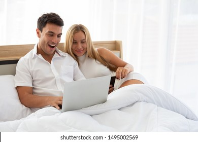 Caucasian couple searching cheap flight ticket and hotel in web online with laptop on bed, Preparing and find amazing accommodations for holidays concept