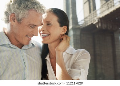Caucasian couple smiling with bridge in the background