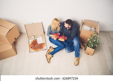 Caucasian couple taking a break, eating pizza and sitting on the floor in new apartment