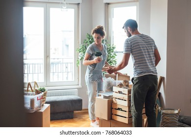 Caucasian couple unpacking boxes at their new home.
