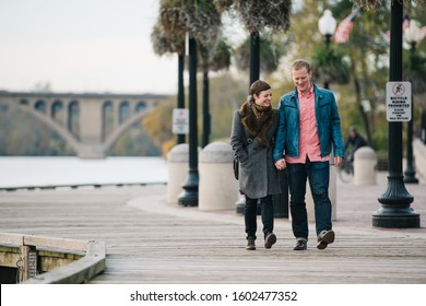 Caucasian couple walking and holding hands while walking the boardwalk in Georgetown, Washington DC with the Key Bridge in the background.