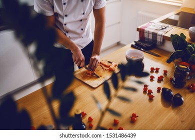 Caucasian creative chef standing in kitchen and cutting salmon for lunch. On kitchen counter are vegetables and spices.