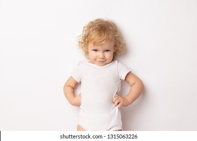 Caucasian curly baby girl in a white T-shirt on a white background hands holding a waist. child hands in hips.