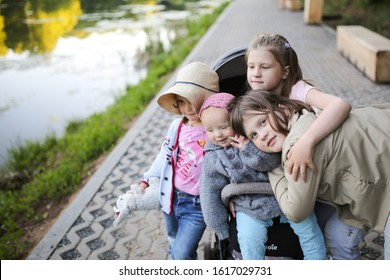 Caucasian cute little girl baby toddler in a stroller in a park and 3 sisters nearby, sisters hug a toddler sitting in a stroller. Concept candid authentic family and 4 children in the family