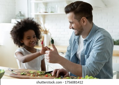 Caucasian daddy African daughter having fun put on fingers cucumber and paprika pieces like puppet toys making up funny vegetable stories while preparing vegetarian natural salad together in kitchen