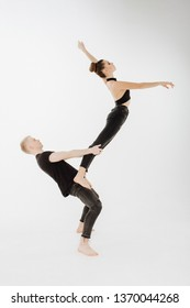 Caucasian Dance Couple Balancing High Level Pose. Man in Demi Plie, Female Dancer Stand on his Hip, Bend, do Arabesque. Young Perfomer in Black do Grase Acrobatic Lift Isolated on White Background