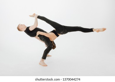 Caucasian Dancing Couple Middle Level Lift Stunt. Blond Man Dancer Hold Upside Down Girl. Beautiful Young Woman doing Side Split. Two Perfomer in Black Form Posing Isolated on White Background