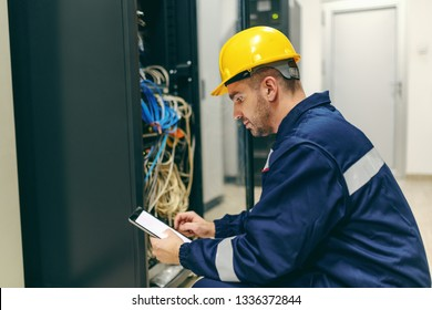 Caucasian dedicated electrician in in uniform and helmet on head using tablet and opening door with dashboard while standing in control room in heavy industry plant.