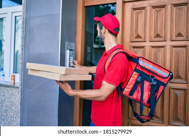 Caucasian delivery man wearing red uniform and delivery backpack smilly happy outdoors holding pizza box