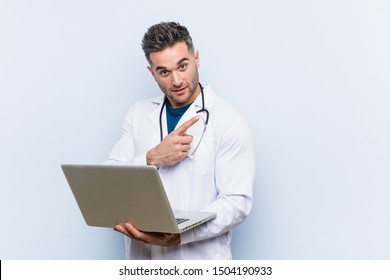 Caucasian doctor man holding a laptop smiling cheerfully pointing with forefinger away.