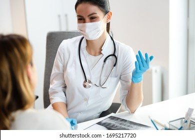 Caucasian doctor in medical mask speaking with mother about scoliosis of her daughter stock photo. Pediatrics concept