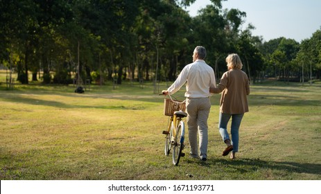 Caucasian elderly couples walking with a bicycle in the natural autumn sunlight garden feel cherish and love, concept elderly love, warm family, Happier Old-Age, retirement lifestyle.