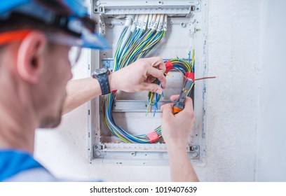 Caucasian Electric Technician in His 30s Installing Electrical System Inside Newly Remodeled Apartment.