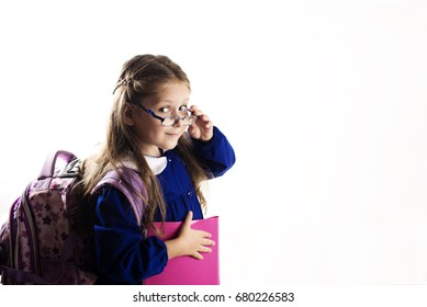 Caucasian elementary age schoolgirl with glasses posing in uniform and backpack on white background. School and education concept