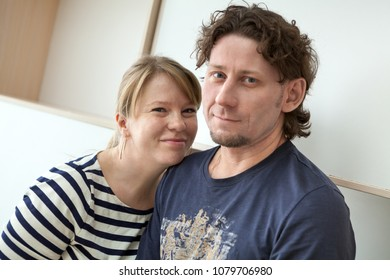 Caucasian embracing couple, man and woman portrait, standing together indoors
