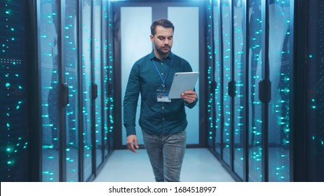 Caucasian IT engineer activating digital database server room with tablet. Bearded specialist inspecting rack internet servers at data center computer security. Zoom out.