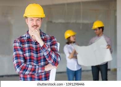 Caucasian engineer wearing yellow safty hat standing and looking to camera. There are two engineers talking in blur background.